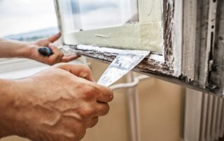 Man using scraper and putty for renovation old windows
