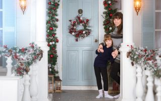 Mom and daughter in cozy home, decorated entrance to house with bright colours. Family waiting for New year. Family photo session in Christmas interiors